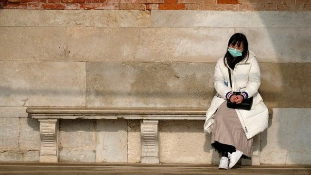 Chinesin mit Gesichtsmaske sitzt einsam auf einer Steinbank.