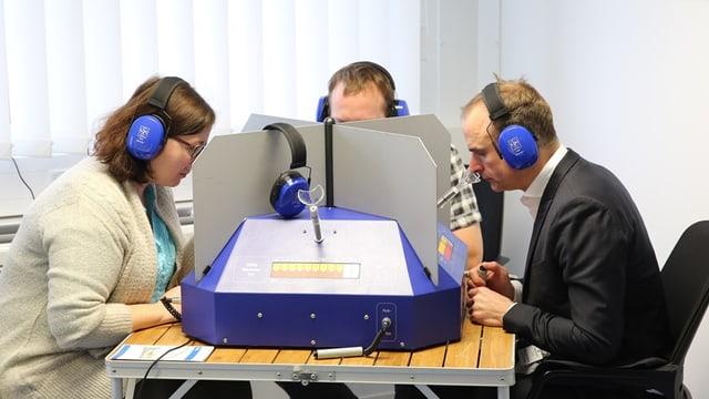 Drei Personen sitzen mit Kopfhörern an einem Tisch, zwischen ihnen hat es Abschrankungen. Sie strecken die Nasen zur Tischmitte, wohl zu einem Computer, den man beim vorderen, leeren Platz sieht.