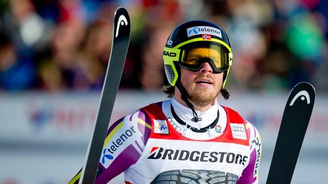 Kjetil Jansrud cun chapellina, spievel d'ir cun skis e ses skis enta maun.