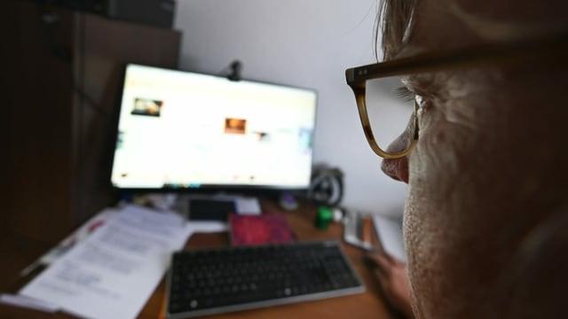 Mann mit Brille sitzt vor Computer