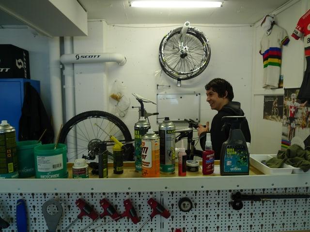Zu sehen ist eine Velowerkstatt mit allerlei Werkzeugen an der Wand aufgehängt, Dosen, Gütterli und Flaschen auf einem Tisch und Velo-Trikots an der Wand.