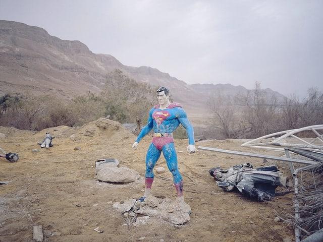 Eine Superman-Figur steht auf einem Minenfeld.