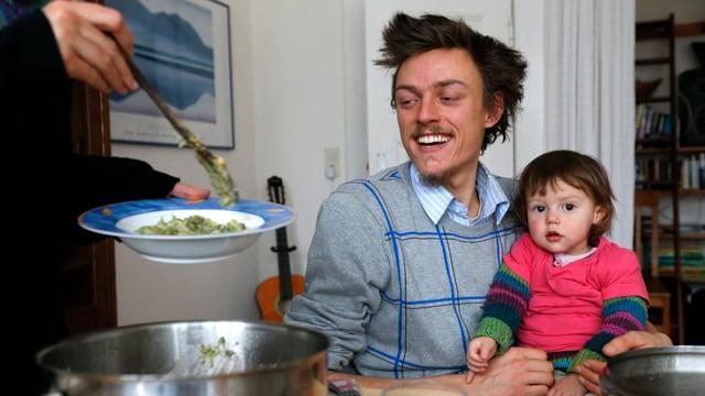 Ein Mann sitzt am Tisch, auf seiner Schoss sitzt seine Tocheter, links steht eine Frau, die Essen in einen Teller schöpft.