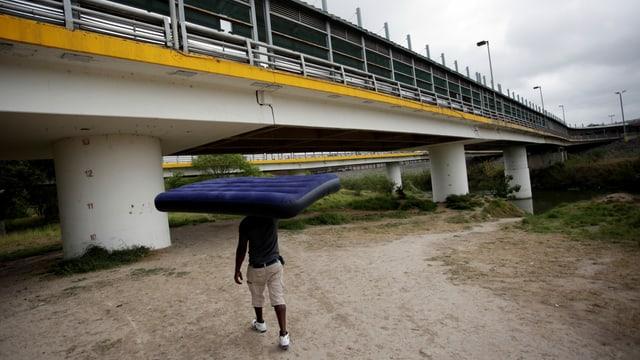 Mann trägt Matratze über dem Kopf in Richtung einer Brücke.