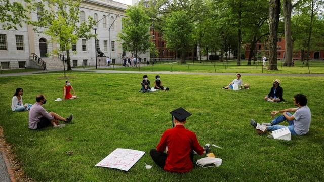 Studenten sitzen mit Maske auf Rasen