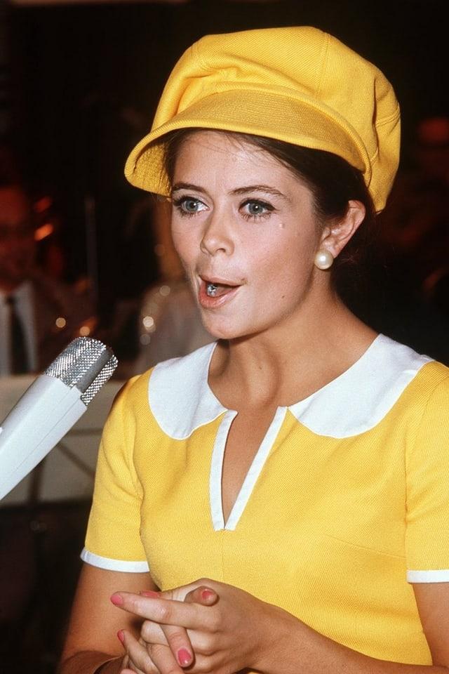 Star singt in Microphon in gelbem Outfit miit keckem Hut.