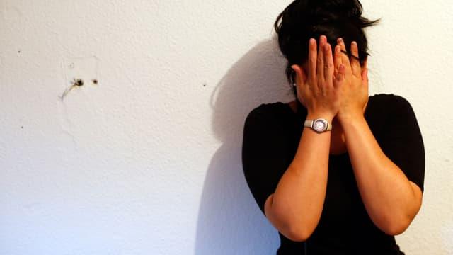 Frau bedeckt das Gesicht mit ihren Händen.