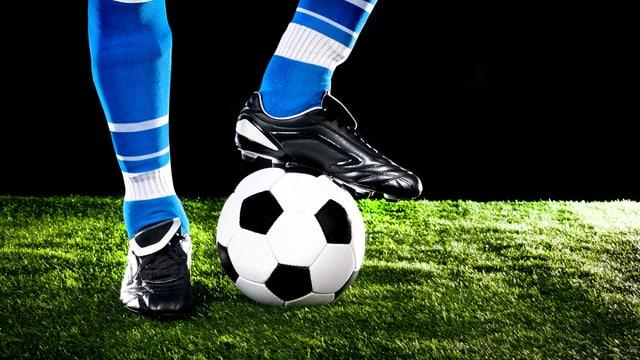 Beine eines Fussballers mit einem Ball