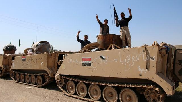 Drei Panzer der irakischen Armee stehen in einer Reihe, auf einem sind drei bewaffnete Männer zu sehen.