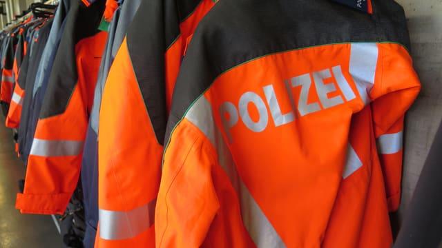 Orange Mäntel der St. Galler Kantonspolizisten hängen in Reih und Glied an der Garderobe.