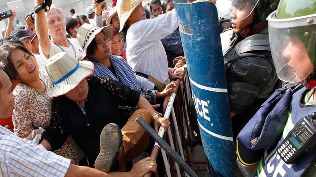 Protestierende Kambodschaner stehen Polizisten in Kampfmontur gegenüber
