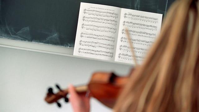 Mädchen mit einer Violine spielt ab einem Notenblatt.