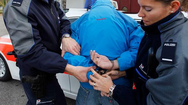 Eine Person wird von zwei Polizisten festgenommen