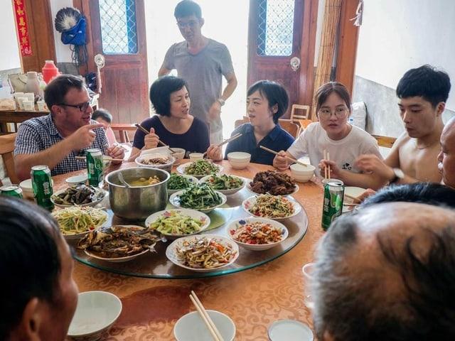 Pascal Nufer am Tisch bei der Familie seiner Haushälterin Changyun Geng auf dem Land in der Provinz Anhui.