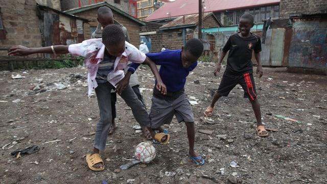 Vier Kinder spielen in einem Hinterhof in Nairobi mit einem selbstgebastelten Fussball.