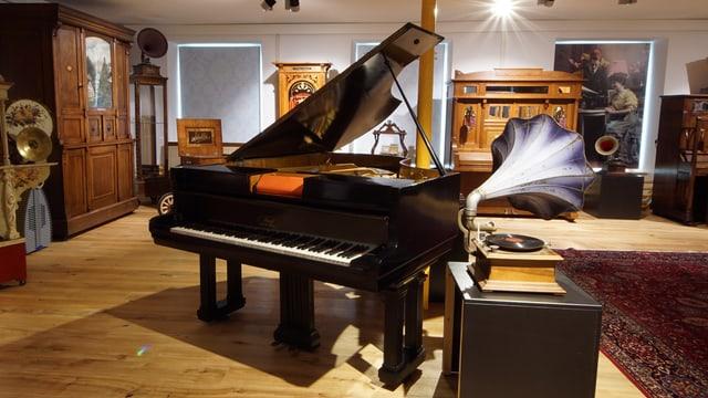Ein Flügel. Daneben steht ein Phonograph mit einem Trichter, der einem Enzian gleicht.