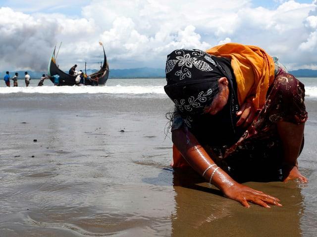 Ein erschöpfte Frau kniet am Boden am Strand.