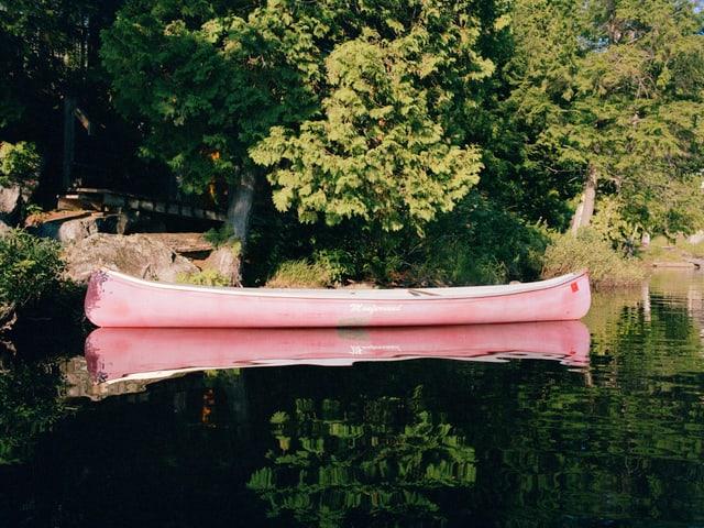 Ein leeres Kanu am bewaldeten Ufer eines Sees.