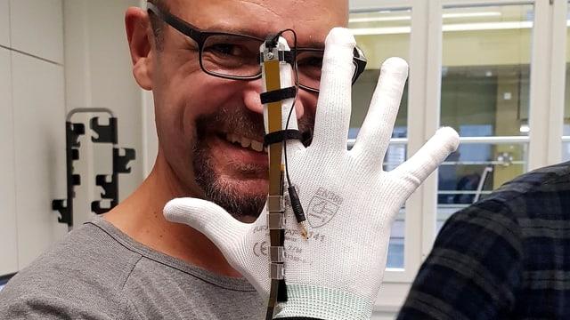 Reto Widmer hält eine Hand hoch mit einem weissen Handschuh, der an einem Finger ein schmales Metallband hat, das als Bremse dient.