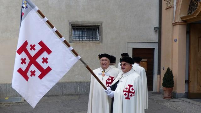 Männer in weissen Roben tragen eine Fahne mit einem aufgestickten Jerusalemkreuz.