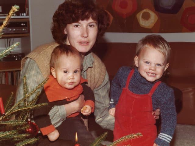 Eine Mutter mit zwei kleinen Kindern neben einem Weihnachtsbaum.