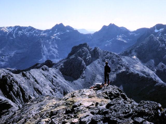 Eine Person auf einem Gipfel schaut auf schwarze, felsige Bergketten.