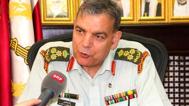 Brigadier-General Saad Jaber in einem Büro. Mit im Bild das Mikrofon von SRF Auslandkorrespondentin Susanne Brunner.
