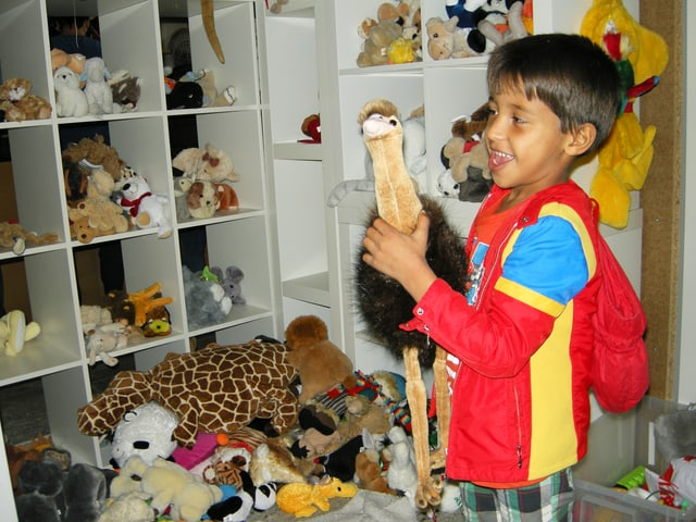 Kind vor einem Regal mit vielen Plüschtieren. Eines hält es lächelnd in der Hand.