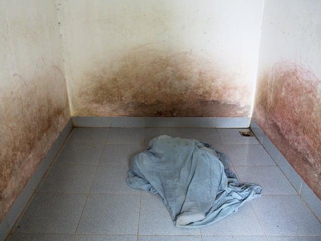 Frau liegt auf blankem Boden und hat sich komplett mit einem Laken bedeckt.