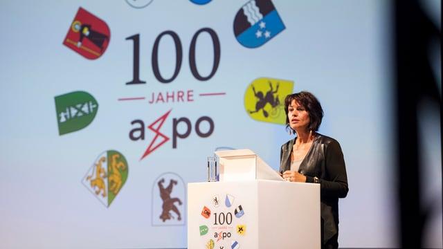 Bundesrätin Doris Leuthard referiert an der 100-Jahr-Feier des Unternehmens im August 2014. Am Rednerpult sind die Wappen der neum Kantone zus ehen, denen die Axpo gehört.n
