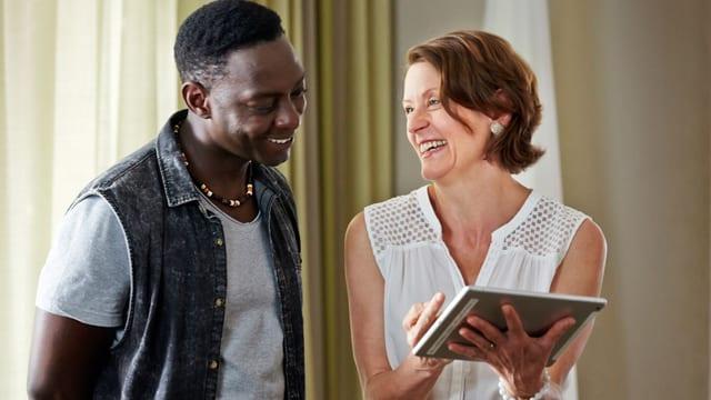Ein schwarzer Mann lacht mit einer weissen Frau über etwas, was sie sich auf dem Tablet anschauen.