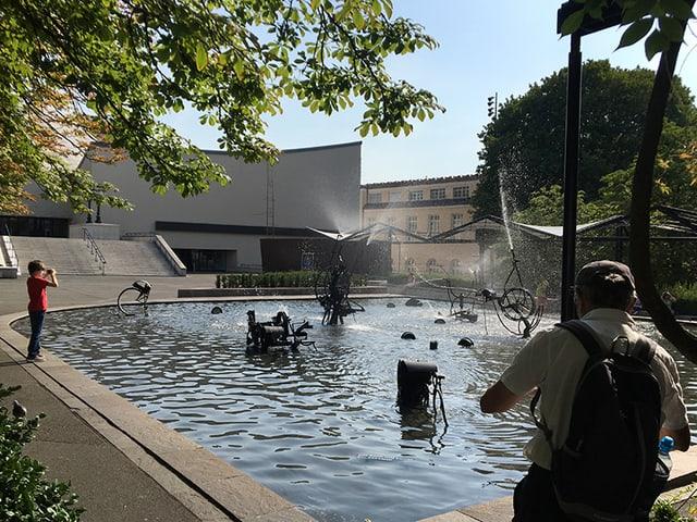 Brunnen mit Metallskulpuren, im Hintergrund Kunstwerk aus Metallplatten.