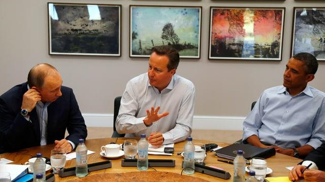 Putin, Cameron und Obama sitzen an einem Tisch und sprechen miteinander.
