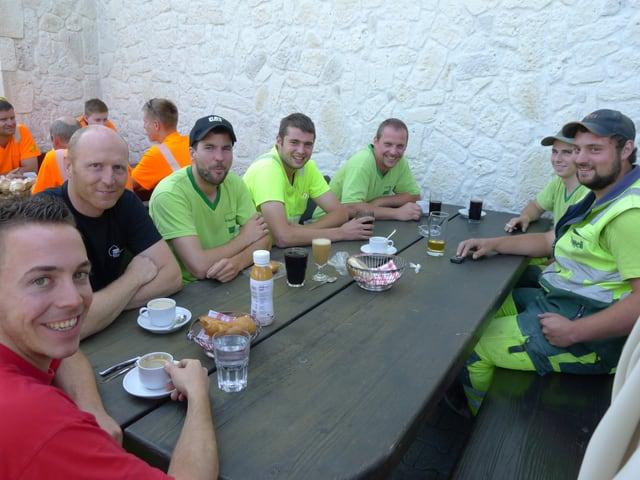 Bauarbeiter an einem Tisch.