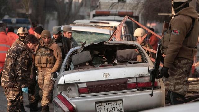 Soldaten und Spezialisten sichern den Tatort vor dem Restaurant in Kabul.