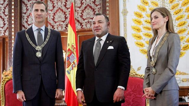 Felipe, Mohammed und Letizia stehen stramm vor roten Sesseln und einer spanischen Flagge.