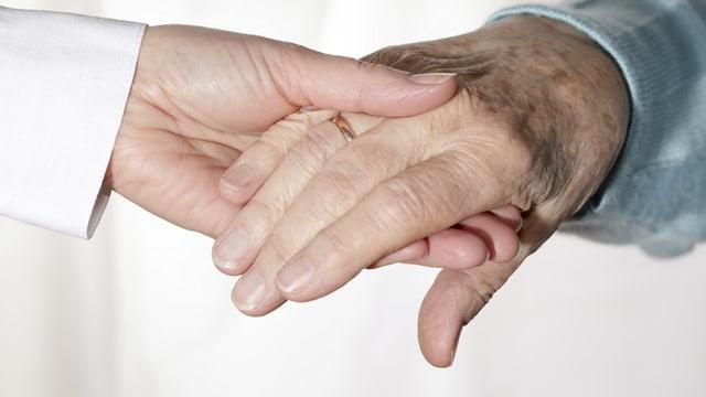 Die Hand einer jüngeren Frau hält die einer alten Frau.