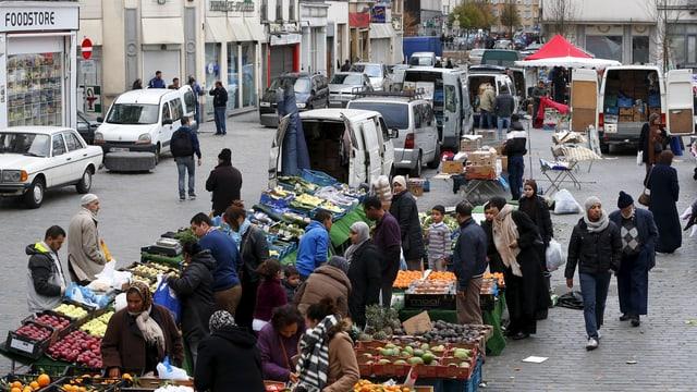 Früchte und Gemüse aufgereiht in Plastikkisten, Menschen stehen darum herum, viele offensichtlich muslimische Ausländer.