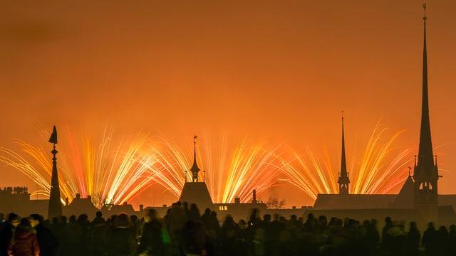 Feuerwerk vor orangem Hintergrund über Stadt Zürich