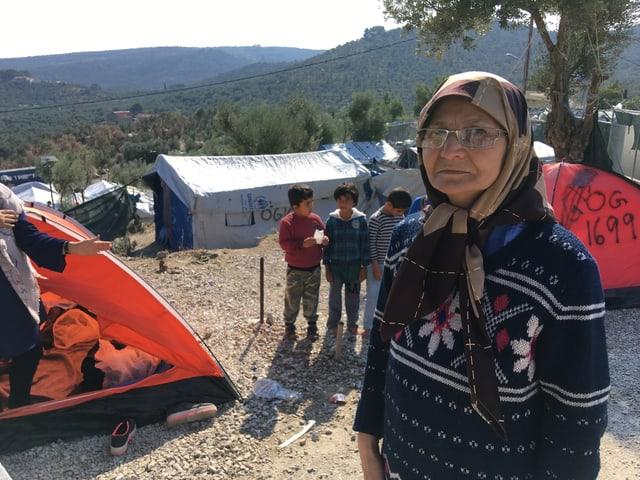Ältere Frau mit Kopftuch und einer Brille, die vor einem roten kleinen Zelt für das Foto posiert.