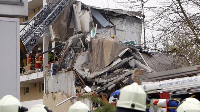 Zusammengebrochenes Haus, Kran hebt Betonelemente auf, Feuerwehrmänner schauen zu