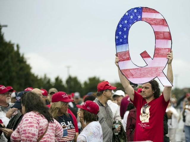 Ein Mann hält in einer Menschenmasse ein grosses Q hoch.