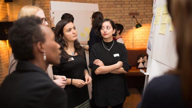 Vier Frauen stehen um ein Flip Chart und diskutieren.