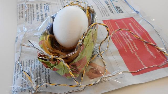 Ein Ei liegt in einer Kartonschachtel.