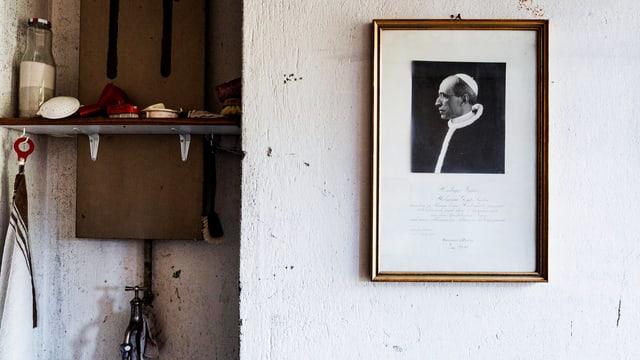 Eine Wand mit einem Bild des Papstes, golden eingerahmt.