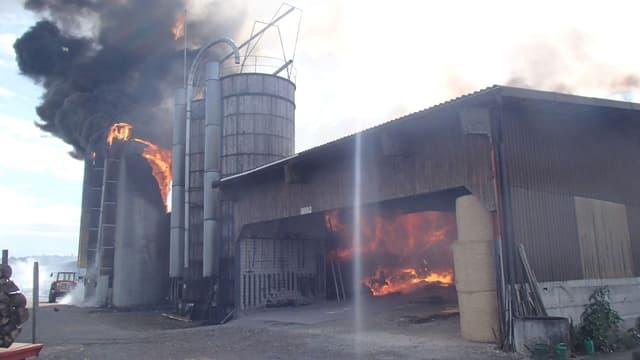 Zu sehen ist ein Stall sowie mehrere Silos, die brennen.