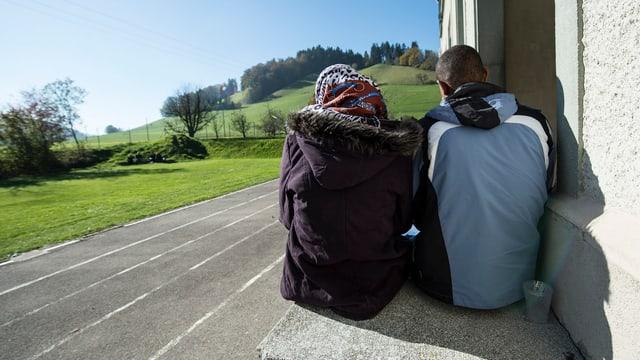 Zwei Asylsuchende von hinten, sie sitzen auf einem Absatz vor der Asylunterkunft in Schafhausen.