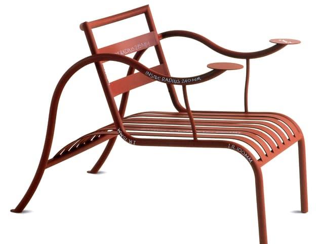 Ein geschwungener Sessel aus Stahlrohr versehen mit flachen Metallprofilen an der Rückenlehne und Sitzfläche.