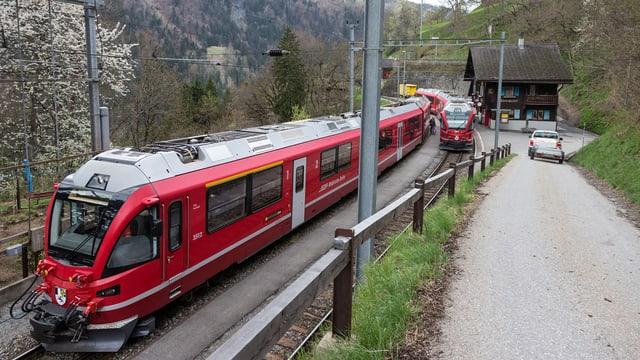 Ein Zug der rhätischen Bahn, im Hintergrund ein Bahnhof.