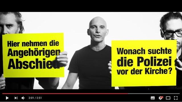 Zwei von drei Männern im schwarzen T-Shirt halten ein gelbes Plakat mit Blick-Schlagzeilen darauf.